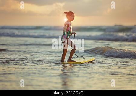 Los jóvenes surfer paseo en tablas de surf con la diversión en las olas del mar.