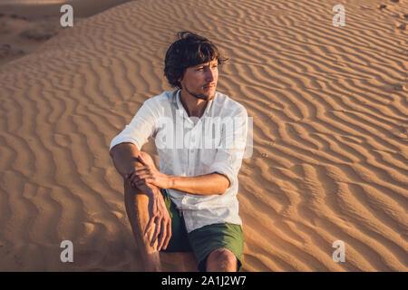 Un hombre se sienta en la arena en el desierto.