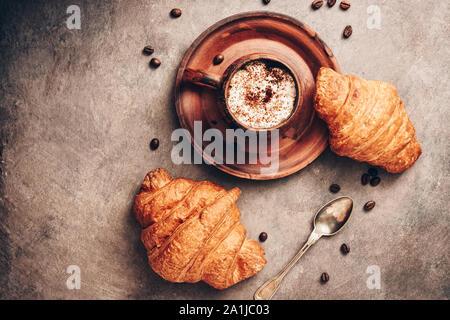 Los cruasanes y café caliente en una taza vintage oscuro sobre un fondo de textura rústica en tonos marrones. Vista desde arriba, laicos plana