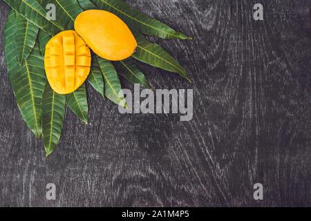 Mango y hojas de mango sobre un fondo de madera vieja. Foto de stock