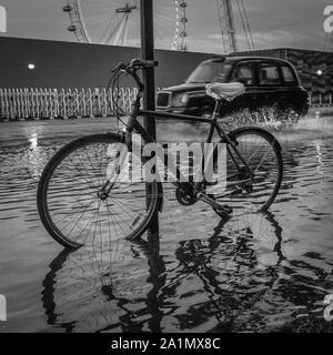 Un icónico black cab de Londres a través de las salpicaduras de agua de inundaciones tras las fuertes lluvias en Londres.