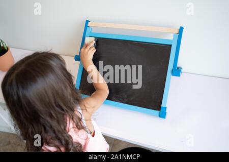 La pequeña niña con cabello marrón largo borrar pequeña pizarra blanca con alrededores visto desde atrás
