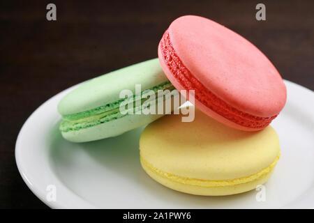 Cerca de las tres de color sobre un fondo blanco macarons plato, postre típico francés.