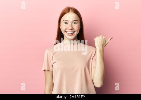 Impresionante positivo adolescente con alegría expresión puntos aparte, muestra el espacio libre para publicidad, vestida con camiseta rosada casual, no puedo creer en