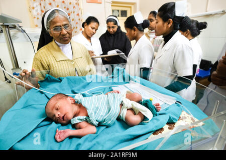 Los médicos y enfermeras hermanas en la cama de un bebé prematuro en el hospital católico en Dhekiajulil Nidas Seva. Estado Federal de Assam, al noreste de la India, Asia