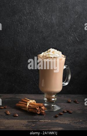 Café irlandés con crema batida sobre fondo de madera negra, copie el espacio.