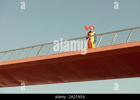 Una espeluznante payaso luciendo un colorido amarillo, rojo y azul del traje, sosteniendo un globo rojo en su mano, de pie en un puente al aire libre