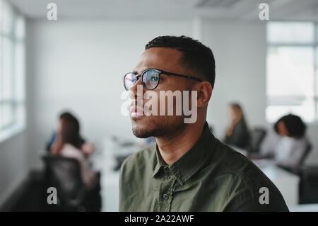 Primer plano de un hombre de negocios americano africano joven empresario el uso de anteojos, contemplando en Office
