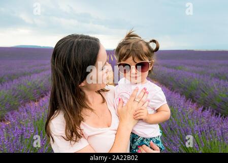 Feliz madre e hija caminando entre campos de lavanda en el verano