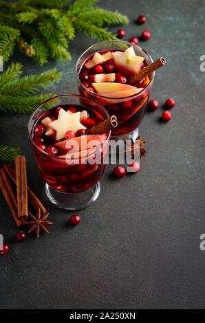 Vino especiado de navidad con manzana, naranja y arándanos. Concepto de vacaciones decorado con ramas de abeto, arándanos rojos y especias.