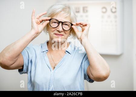 Retrato de una mujer de más edad feliz el uso de anteojos en la parte delantera de la tabla optométrica en oftalmología office. Concepto de control de vista y seleccionar gafas
