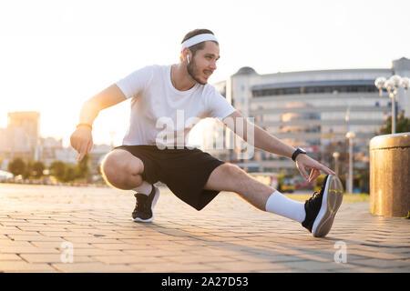Macho joven atleta emparejador capacitación y haciendo ejercicio al aire libre en la ciudad.