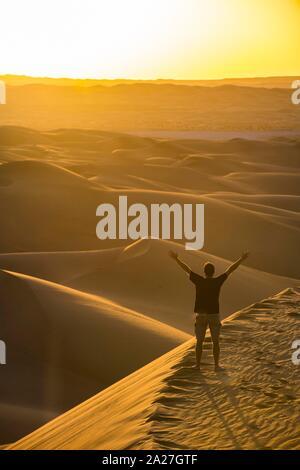 El hombre disfruta de la puesta de sol en el gigante sanddunes del Sahara Timimoun, Argelia