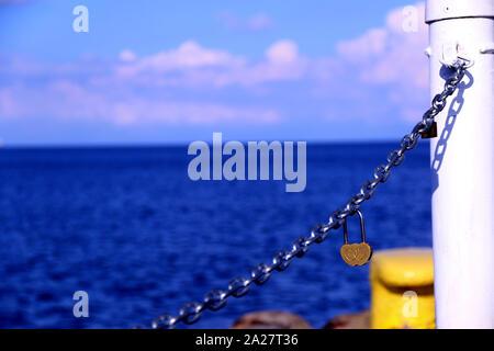 Un corazón con forma de candado en la cadena de hierro