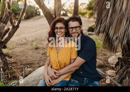Matrimonio adulto medio sentado sobre una roca sonrientes que se abrazan cerrar
