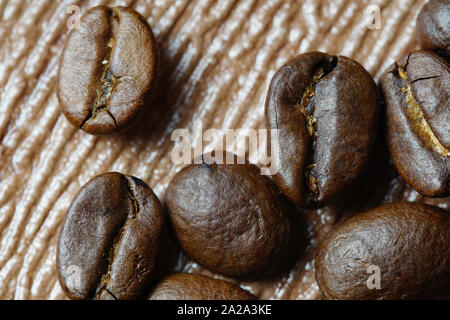 Cerca de los granos de café sobre fondo de madera