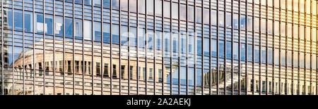 Panorámica de un edificio moderno de vidrio al atardecer con las nubes reflejándose en las ventanas de vidrio