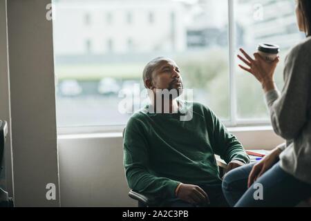 Diseñador americano africano hablando con un colega en el trabajo