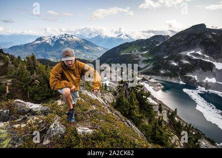 Un hombre caminatas a lo largo de una cresta alpino en las montañas.
