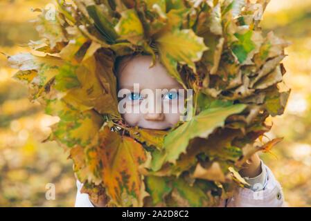 Poco niño niña jugando con hojas de arce corona