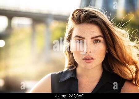 Retrato de hermosa mujer joven con pecas en su cara , mirando a la cámara. Chica con pelo largo y maquillaje natural.