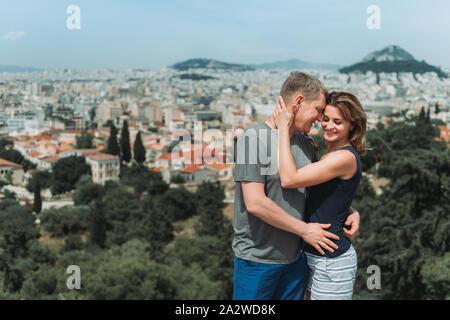 Par el hombre y la mujer en la cima de la montaña disfrutando de paisaje hermoso paisaje Atenas Grecia en segundo plano. Los turistas relajarse en la colina Atenas en verano. La famosa ciudad de Atenas en Europa. vacaciones activas.