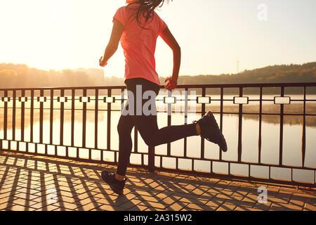 Los corredores piernas corren a lo largo de la carretera por el lago en el parque