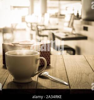 Café caliente y caja de regalo sobre la mesa de madera en el internet café en tonos cálidos Foto de stock