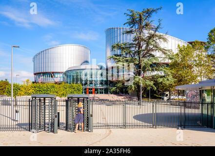 Una mujer en vestido azul está pasando la barrera de seguridad para entrar en el edificio del Tribunal Europeo de Derechos Humanos en Estrasburgo, Francia.