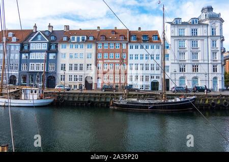Copenhague, Dinamarca - Mayo 04, 2019: coloridas fachadas y restaurantes de Nyhavn terraplén y viejos barcos que navegan a lo largo de la canal de Nyhavn en Copenhague, Dinamarca