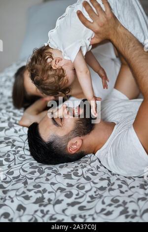 Una joven familia feliz jugando con su bebé mientras está acostado en la cama en casa, sosteniendo kid por encima de sus cabezas . Cerrar vista lateral foto Foto de stock