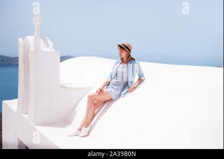 Viajes de lujo vacaciones mujer mirando a ver en Santorini, famoso destino turístico de Europa. Elegante joven que vive fancy jetset lifestyle luciendo vestidos en vacaciones. Increíbles vistas del mar y la Caldera.