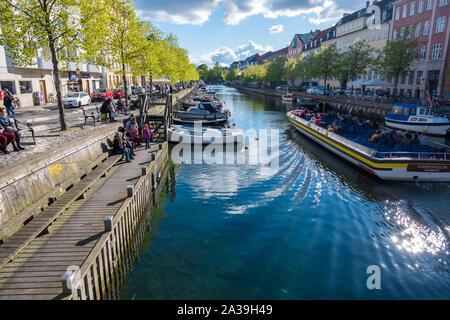 Copenhague, Dinamarca - Mayo 04, 2019: la gente relajarse a orillas del mar, mientras que otros explorar Copenhague en un barco turístico