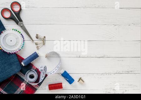 Accesorios de costura, tejido jeans y plaid con hilos de costura, tijeras, alfileres, agujas, botones y costura centímetro sobre un fondo de madera blanca. top