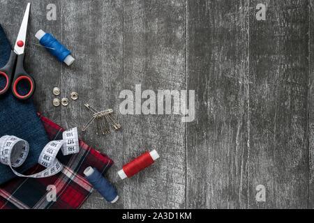 Accesorios de costura, tejido jeans y plaid sobre un fondo de madera oscura. Tela, hilos de costura, tijeras, alfileres, agujas, botones y centímetro de costura