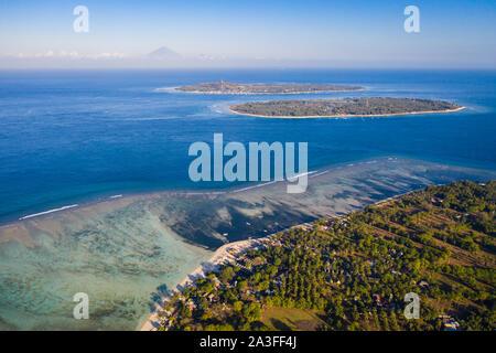 Vista aérea de las tres islas Gili Meno, aire y Trawangan en Lombok en Indonesia, con el volcán Agung de Bali en segundo plano.