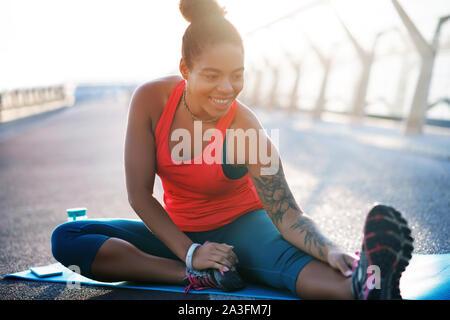 Mujer sonriente sensación increíble al hacer yoga fuera