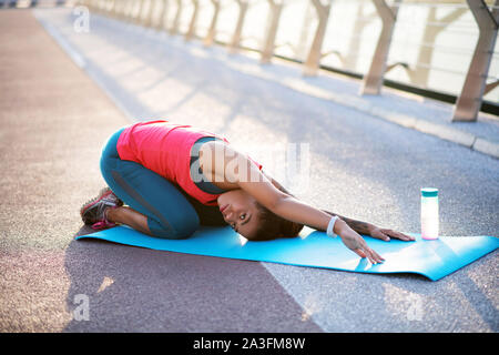 Mujer de piel oscura en el deporte hacer yoga mat, cerca de la botella de agua