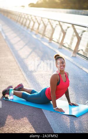 Transmisión de bella mujer haciendo yoga en el puente