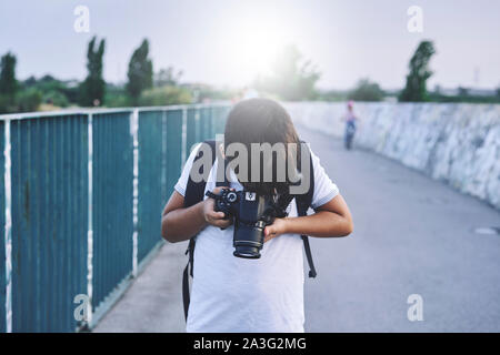 Niño fotógrafo con sombrero blanco tomando fotos con su cámara