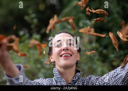 Mujer joven arrojando hojas en un jardín. Foto de stock