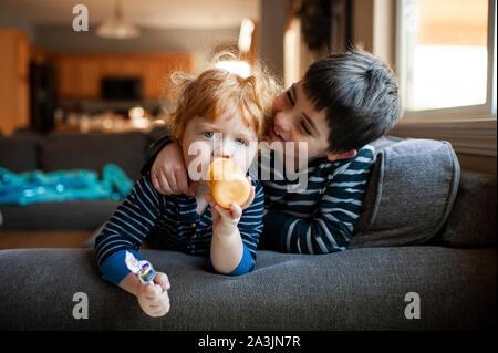 Hermanos sentado en sofá junto con armas uno alrededor del otro en casa