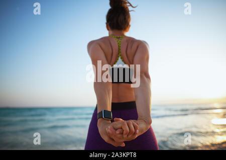 Visto desde detrás de la joven mujer deportiva en ropa de gimnasia en la playa al atardecer de estiramiento.