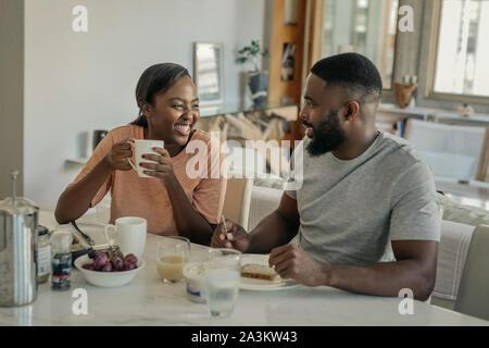 Los jóvenes afroamericanos par riendo juntos durante el desayuno