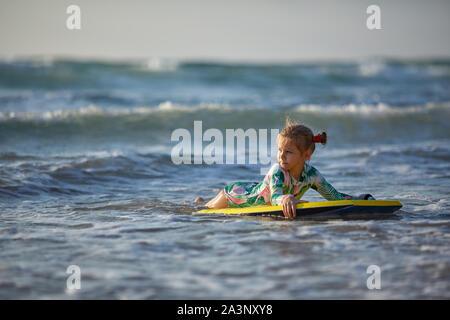 Hijita joven surfista con bodyboard tiene un divertido sobre las pequeñas olas. Estilo de vida familiar activo