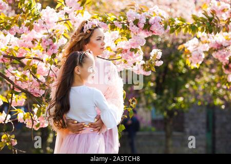 Madre de moda con su hija caminando entre árbol de Sakura. Las mujeres de moda de primavera.