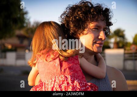 Padre joven sosteniendo a su hija pequeña piscina al atardecer. El hombre está mirando a otro lado mientras el niño está de vuelta ver vistiendo un vestido rojo.