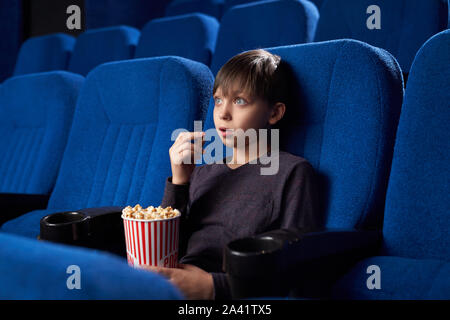 Vista desde el lado del chico emocionado con grandes ojos y boca abierta viendo la película sorprendente en el cine. Conmocionado adolescente masculino comiendo palomitas, mirando la pantalla y viendo el horror. Concepto de ocio y diversión. Foto de stock