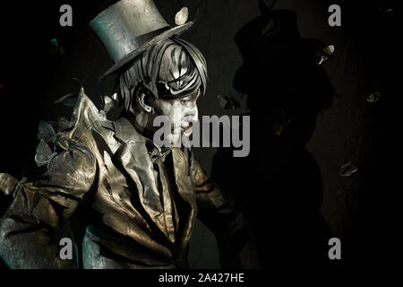Vista lateral del professional pantomimist pintado en traje y sombrero, parado con la pared negra detrás de su espalda y artificial con mariposas volando alrededor. Artista mostrando su habilidad en la improvisación