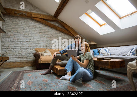 Feliz pareja joven con tablet sentados en el suelo en casa Foto de stock